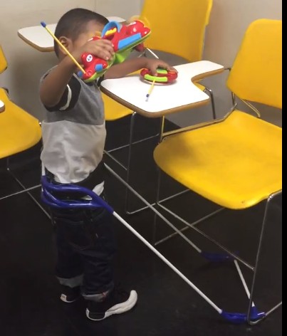 4-year-old stands near chairs with attached desk, visually impaired, wearing belt cane the cane fits under the chair, he is holding remote control airplane and other hand has the controller.