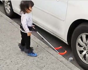 Two year old girl who is blind wearing her cane. She is stopped because her cane tip has fallen off a curb.