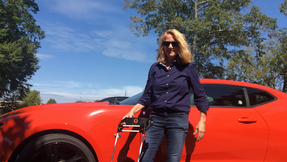Author stands in front of the orange Camaro holding wearable cane