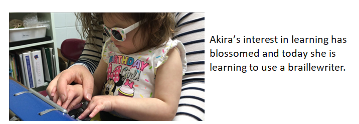 Akira sits at braillewriter being attentive to the lesson