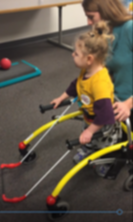 Preschool girl with mobility visual impairment uses her Safe Toddles 'Toddler Cane to walk in a gait trainer down a school hallway to physical therapy room.