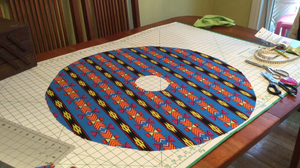 Decorative fabric cut in shape of circle with center circle cut out, lies on a table.
