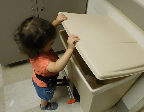 three year old who is blind stands next to a bin and his opening the lid with both hands. She seems to be looking inside. Wearing her belt cane.