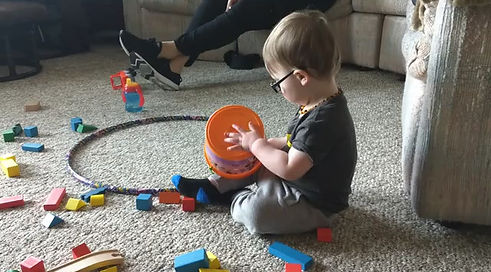 sitting on the floor surrounded by blocks he is playing with a bucket