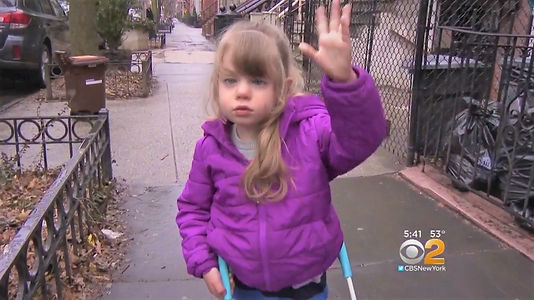 lea wears her cane, one hand holding the cane, one hand waving