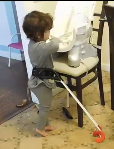 Child wearing belt cane stands near a chair. One hand near her mouth the other touch the chair.