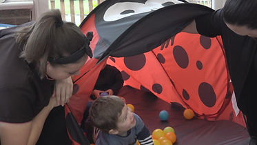 toddler in tent with colourful balls