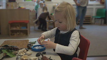 Pre-school child plays with magnifying glasses