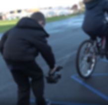 child filming moving bicycle