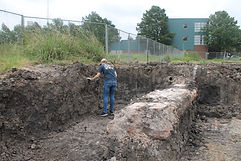 Person looking at dirt with brick structure behind