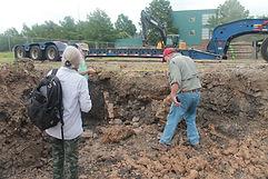 Three people investigate brick structure in dirt