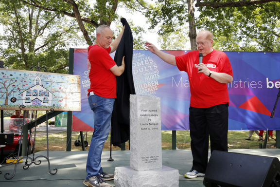 """BCH president /CEO Michael C. Blackwell and BCH chief operating officer Keith Henry unveil a monument honoring Linda Morgan's 45th anniversary. The marker proclaims an area of property at Mills Home as """"God's Canopy,"""" a name Morgan decreed in 2005 for the tree-covered area that provides a cool, shaded spot for Family Gathering and other events."""
