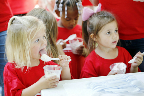 Weekday Education girls cool off eating ice cream provided by Trustee Jim Jacumin.