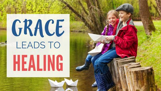 Children laughing making paper boats at lake