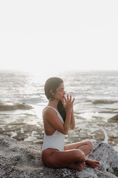 woman-wearing-white-swimsuit-meditating-
