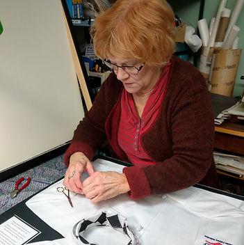 Owner Rebecca Sommer framing a chefs uniform.