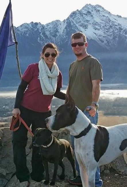 man and woman standing with large black and white dog, and a smaller black dog with a mountain backg