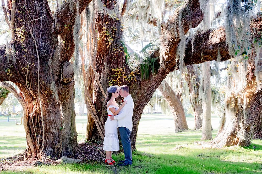 couple kissing under spanish moss in savannah wedding