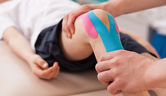 man manipulating a leg with kinesiology taping