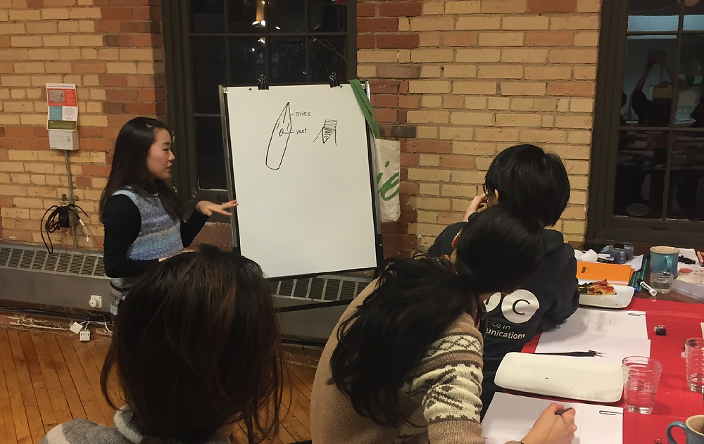 Sarah Kim explaining the different tools used in calligraphy.