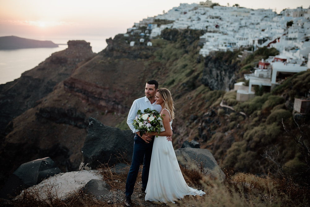 bridal couple standing at the cliffs on Santorini