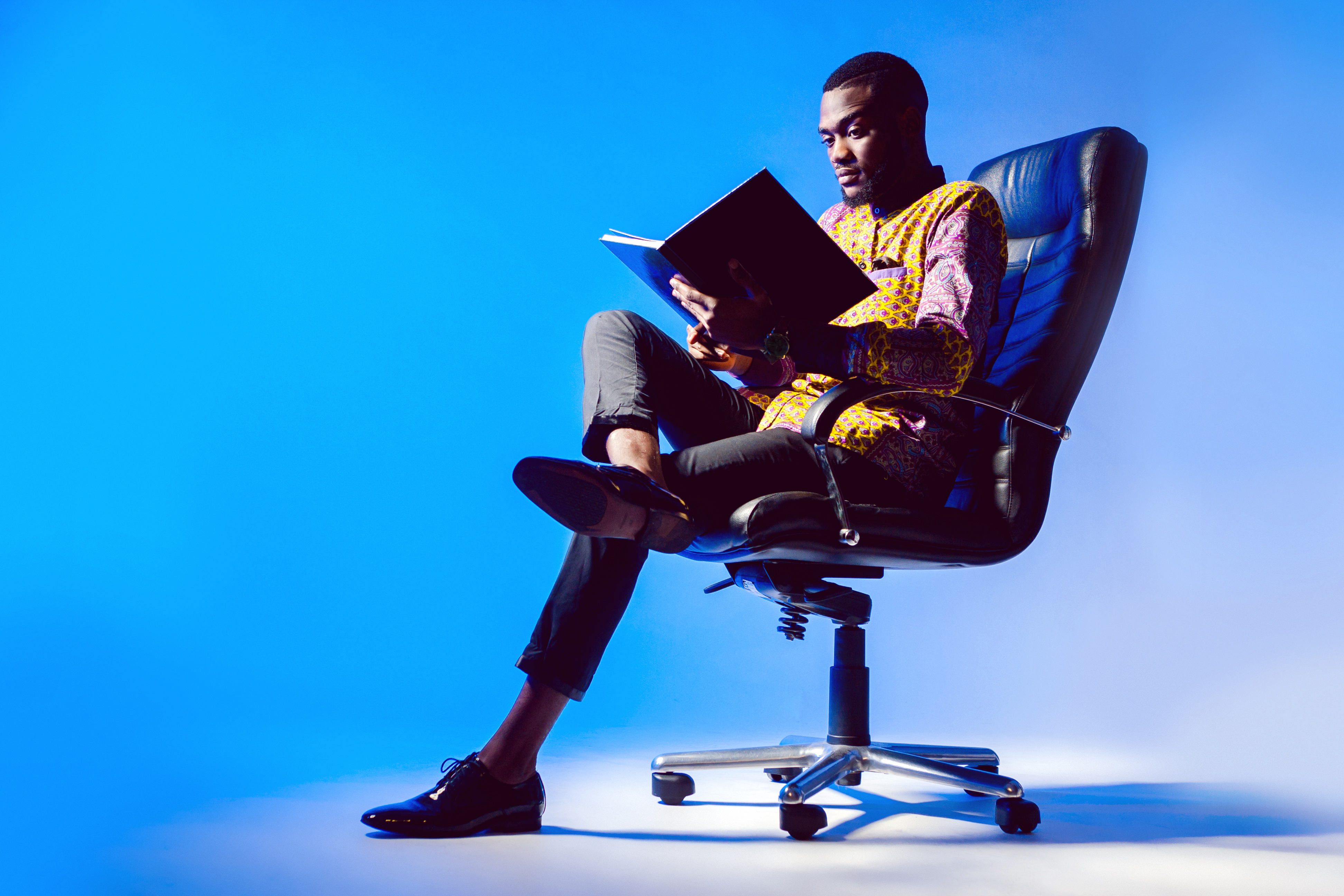 A black man is reading a book.jpg A man is reading a book in a chair