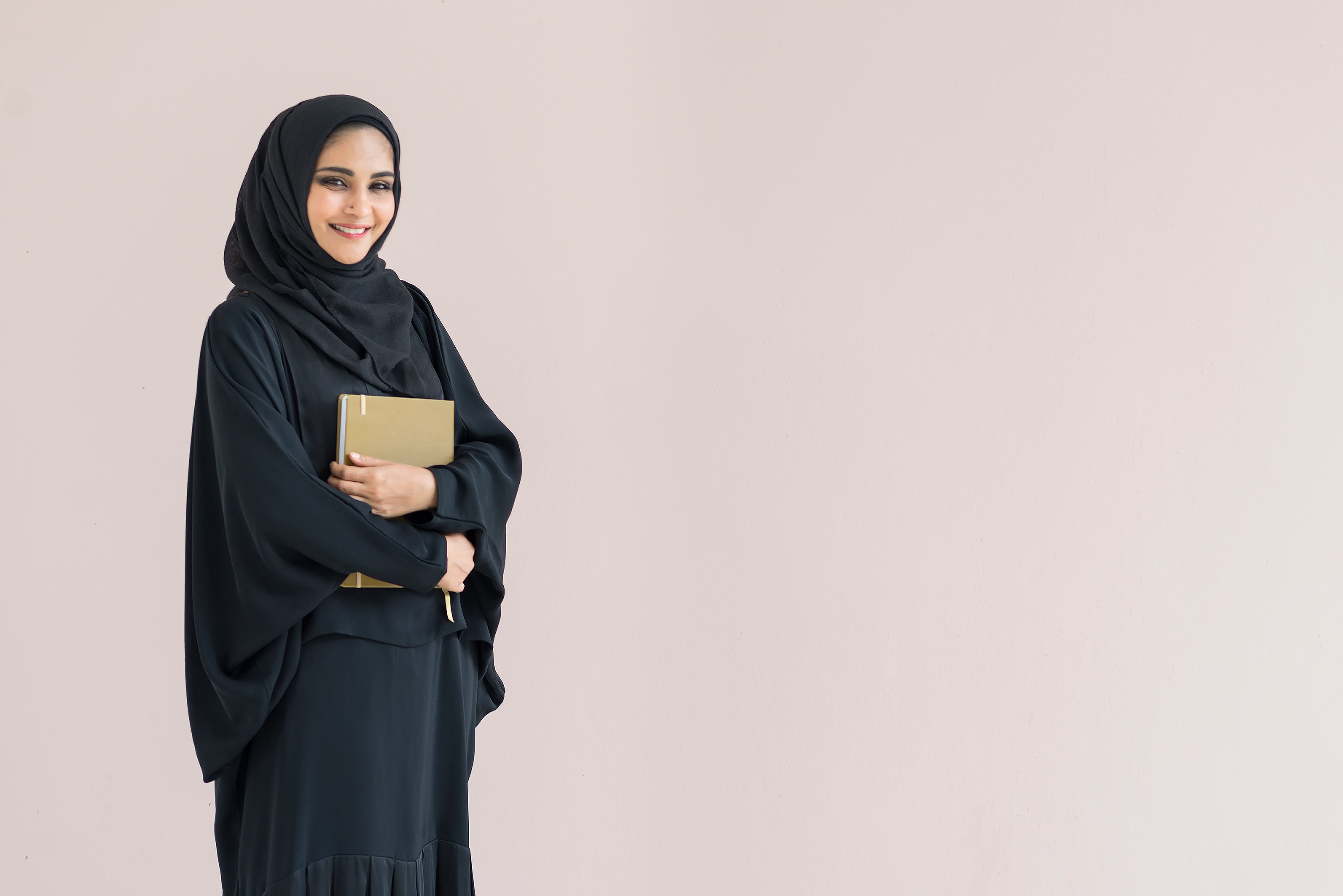 Arabian woman standing and holding a book