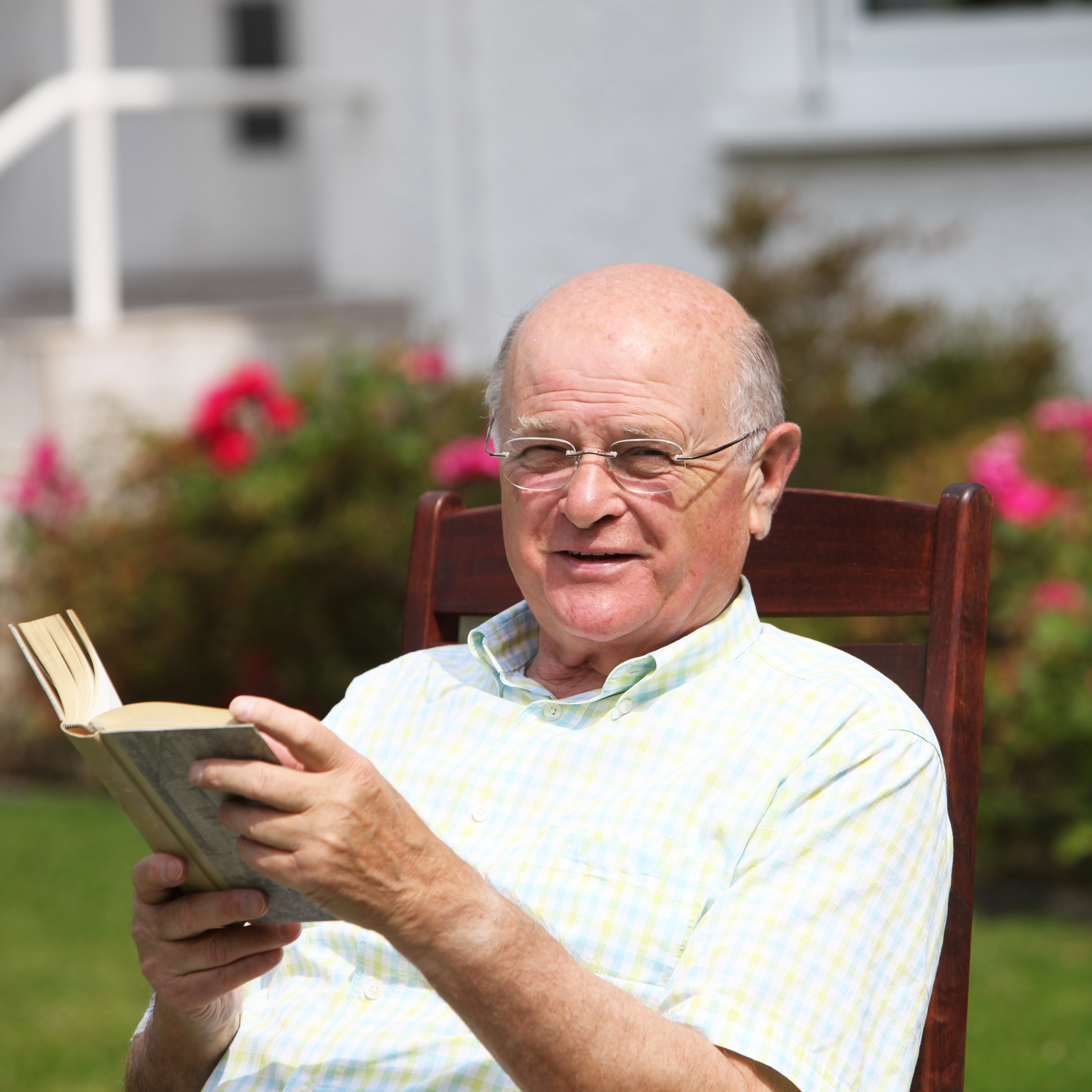 Happy pensioner relaxing with a book Happy pensioner relaxing with a book sitting in his garden enjo