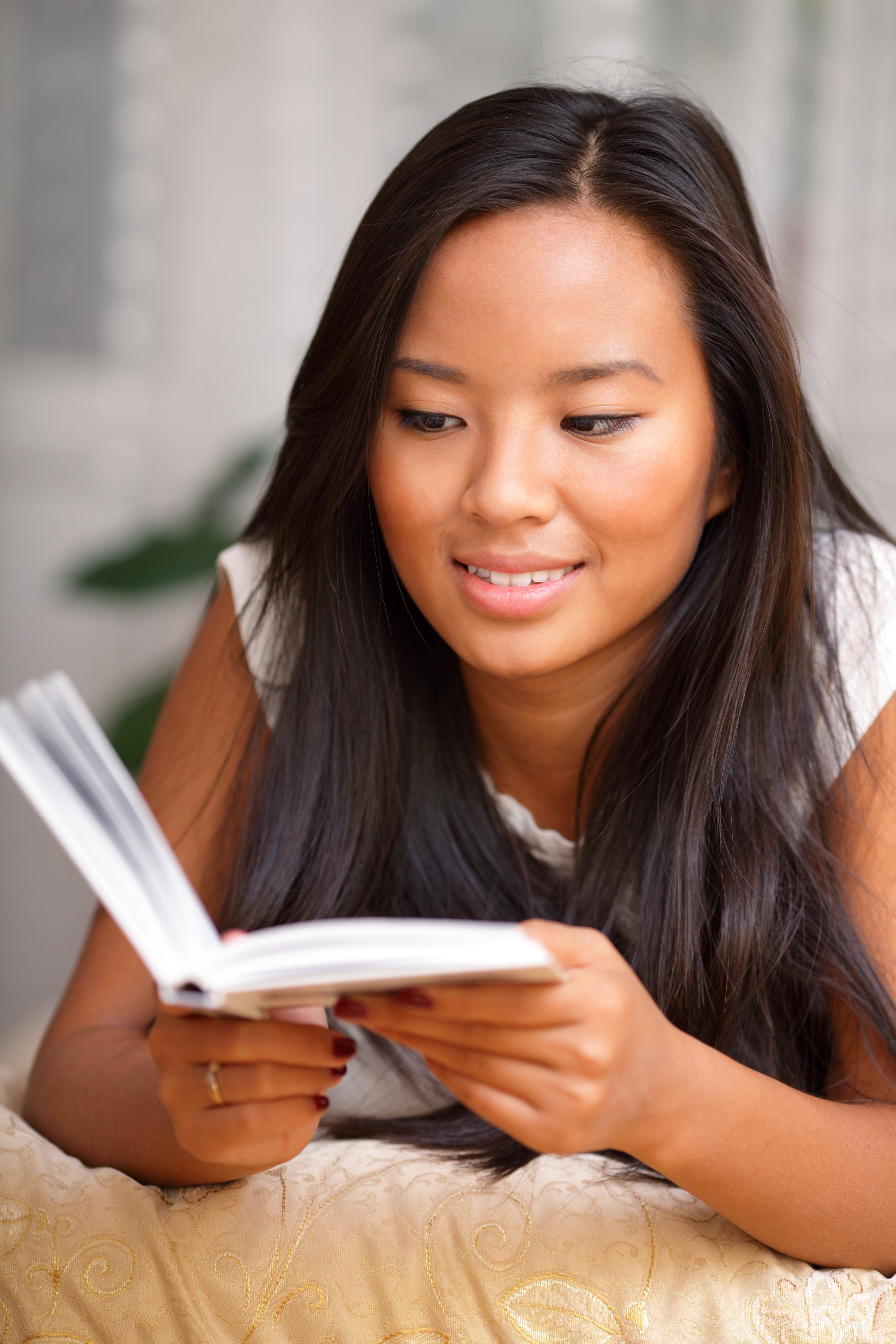 Young asian woman reading a book at home