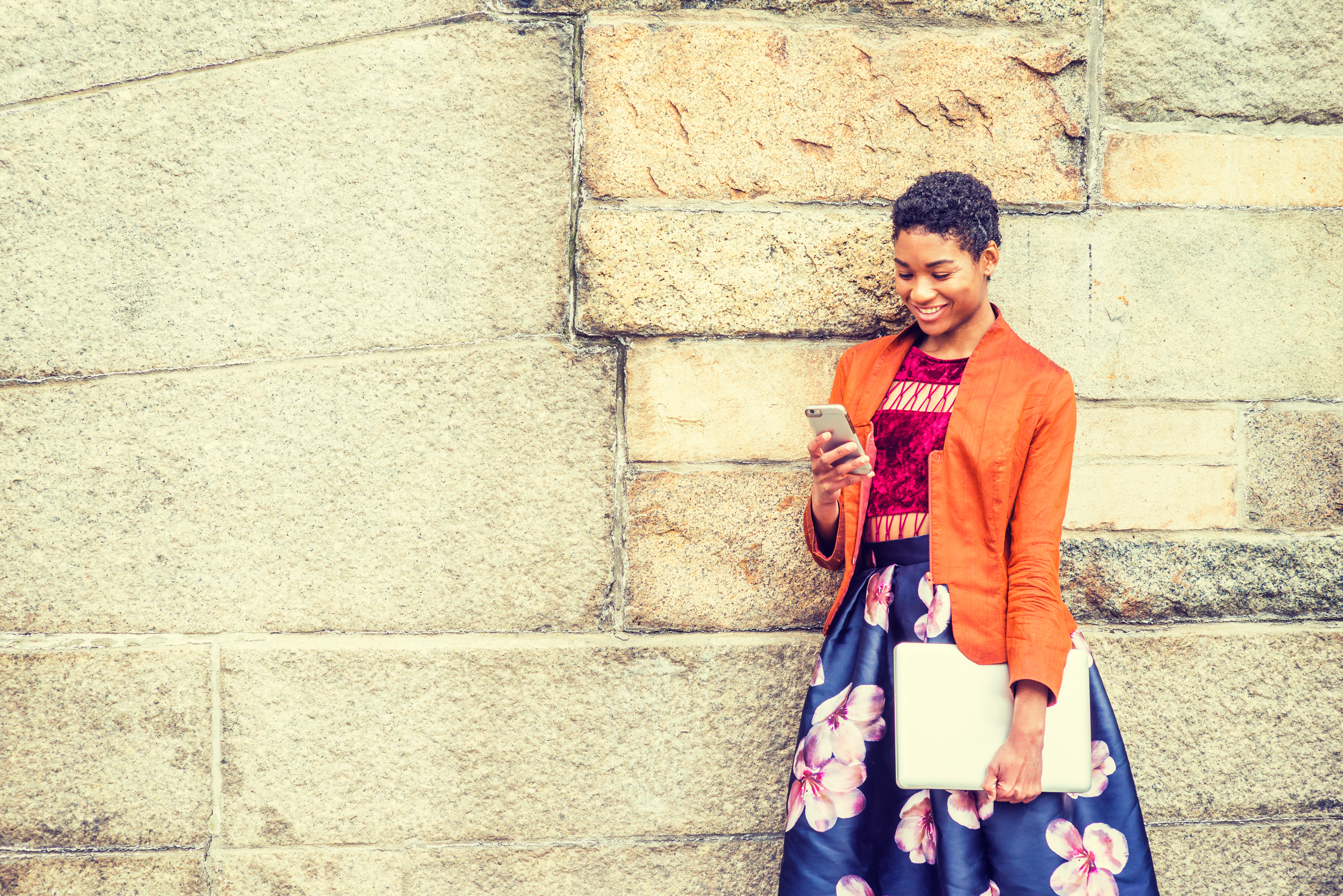 Happy Young African American Woman texting on cell phone outside in New York, wearing orange red jac