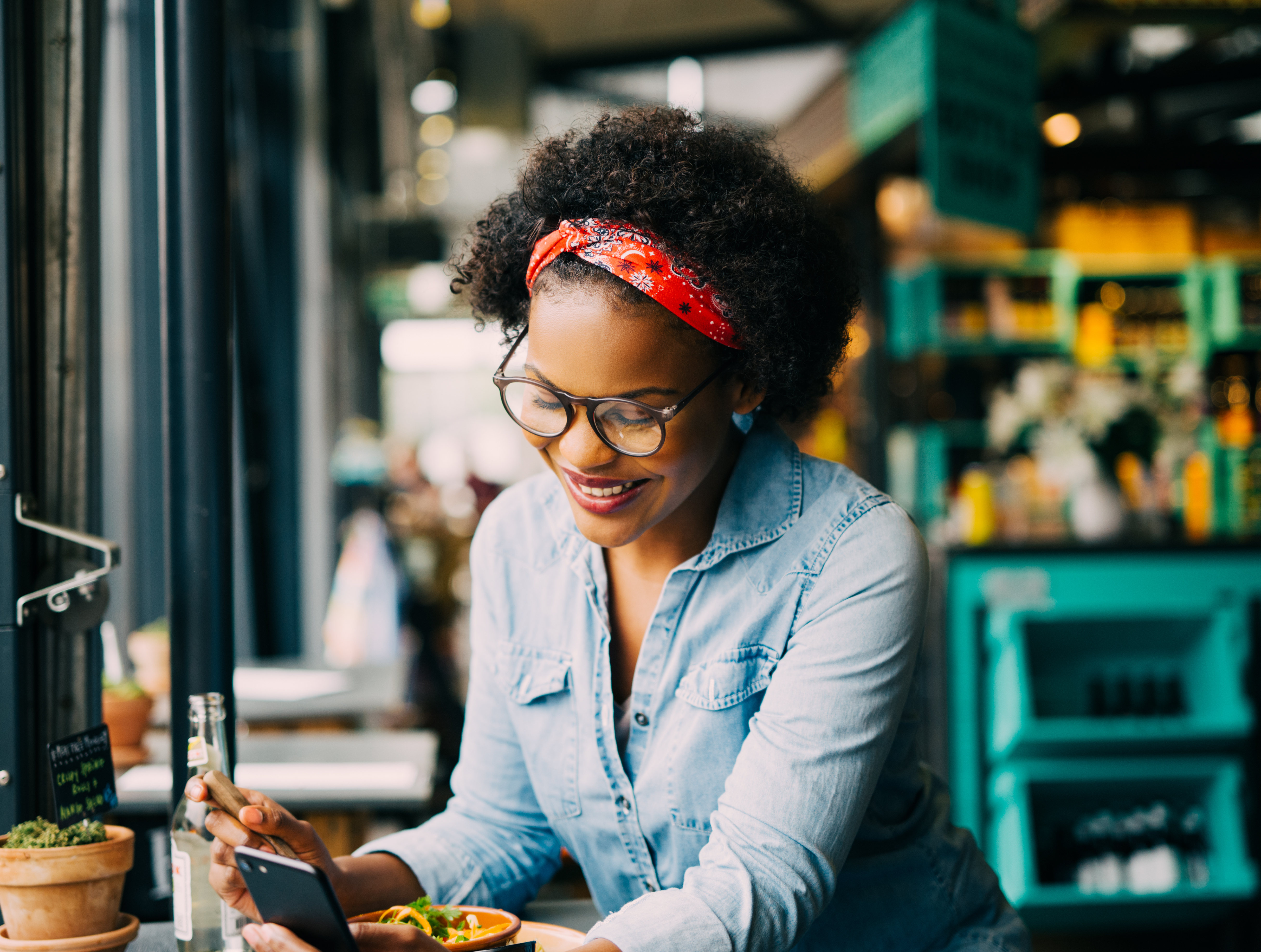 Smiling young African woman reading texts on a cellphone while sitting alone at a counter in a cafe