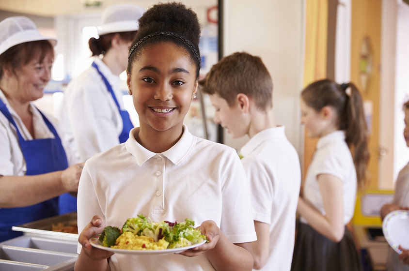 Black schoolgirl holds a plate of food i