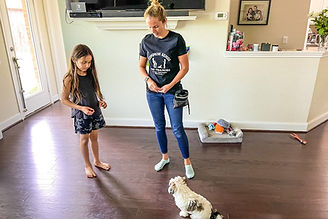 Trainer is showing young girl how to teach her dog to sit inside the home.