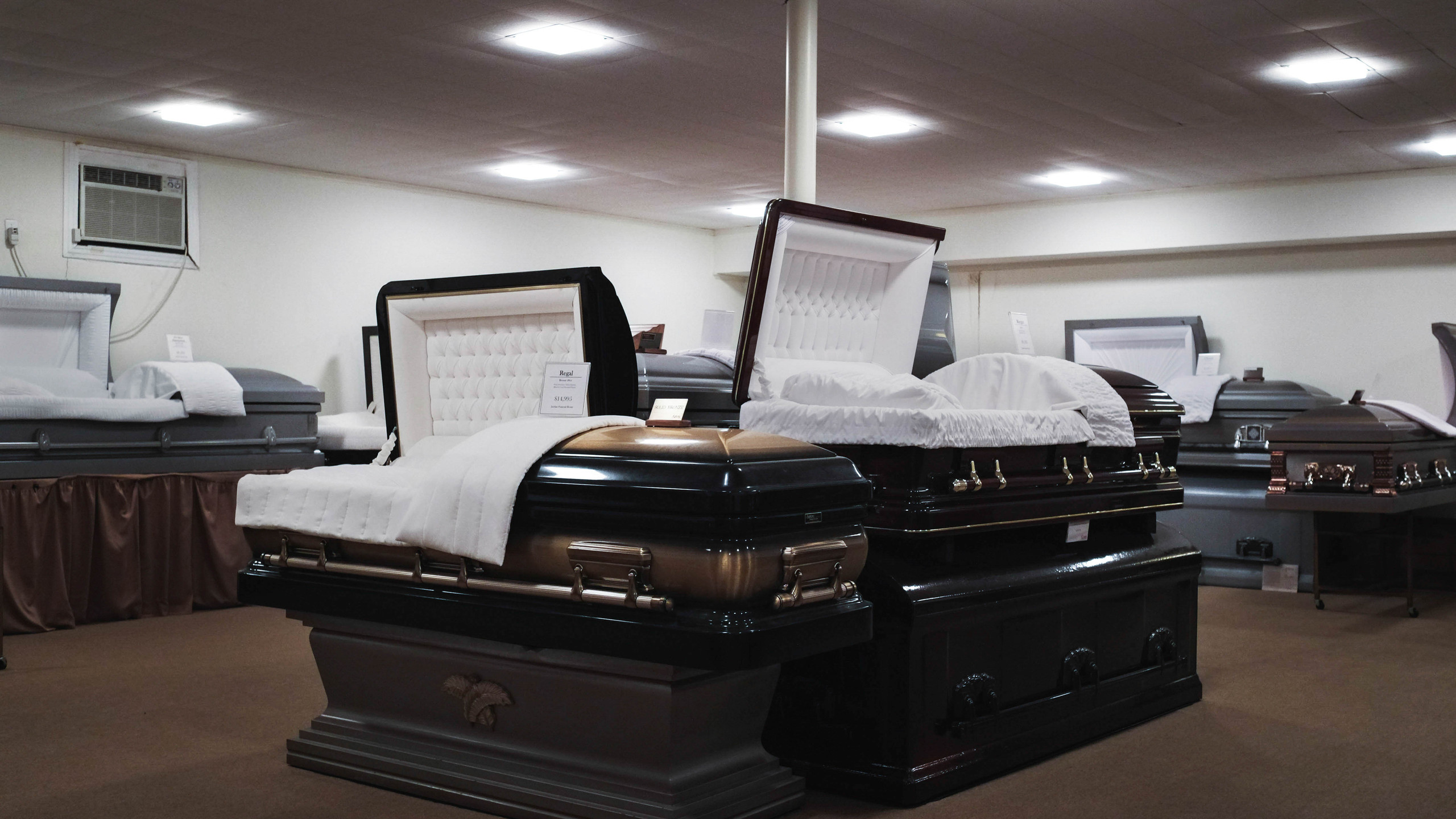 Caskets are displayed in a showroom for the decedents' families to purchase.