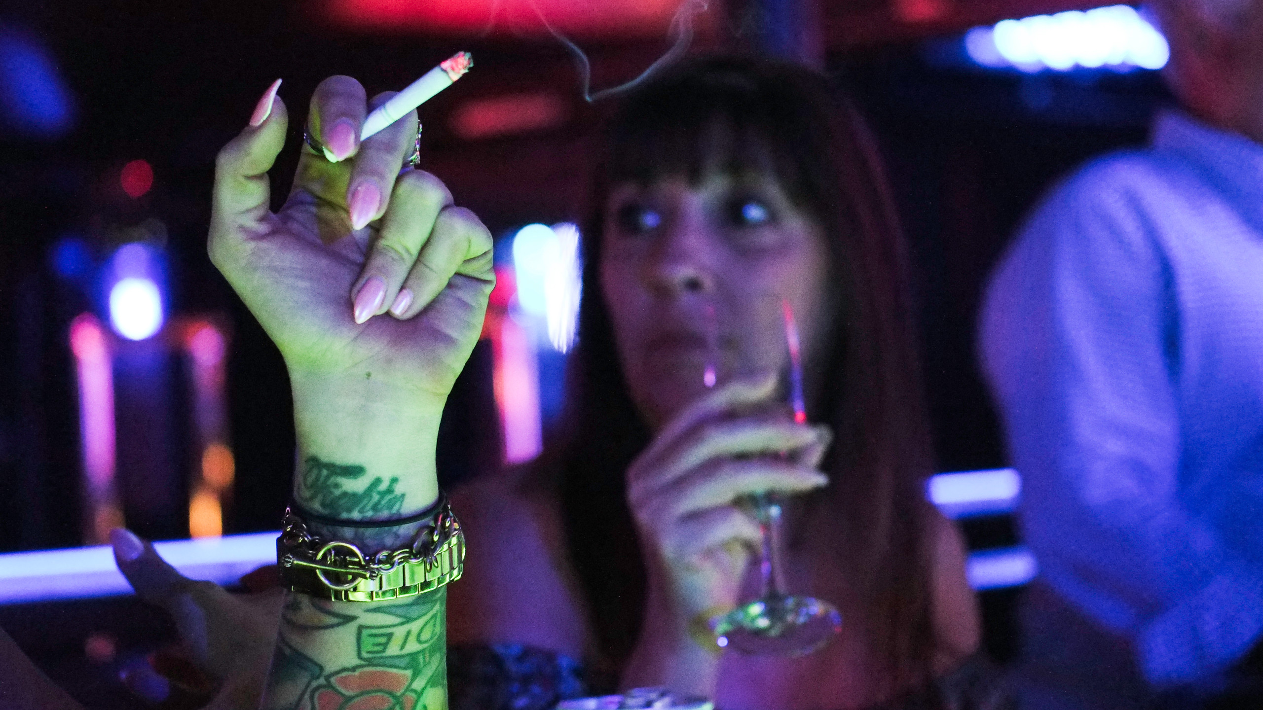 Smoking and drinking are a large part of the strip club experience. Dancers are encouraged to have customers buy them drinks in order to increase the club's profits. Here, Charleen and Jet are seen smoking and drinking at the bar.