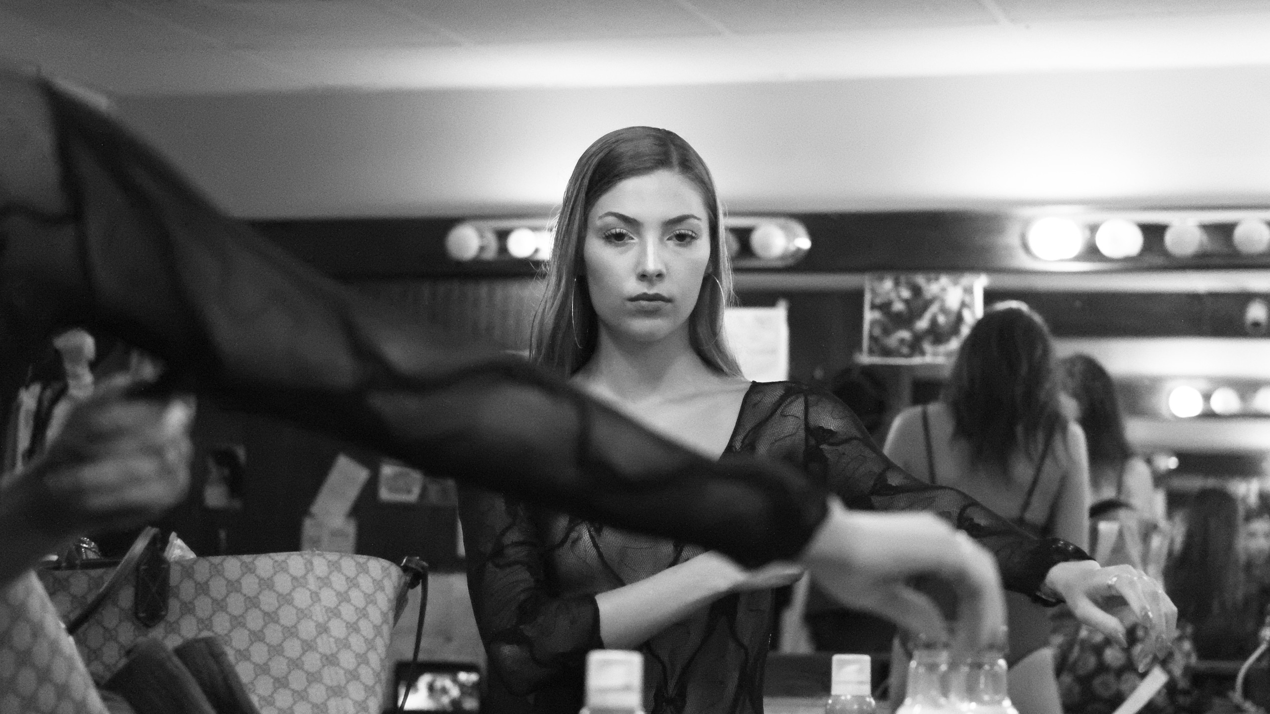 Adriana changes into her work clothes backstage.