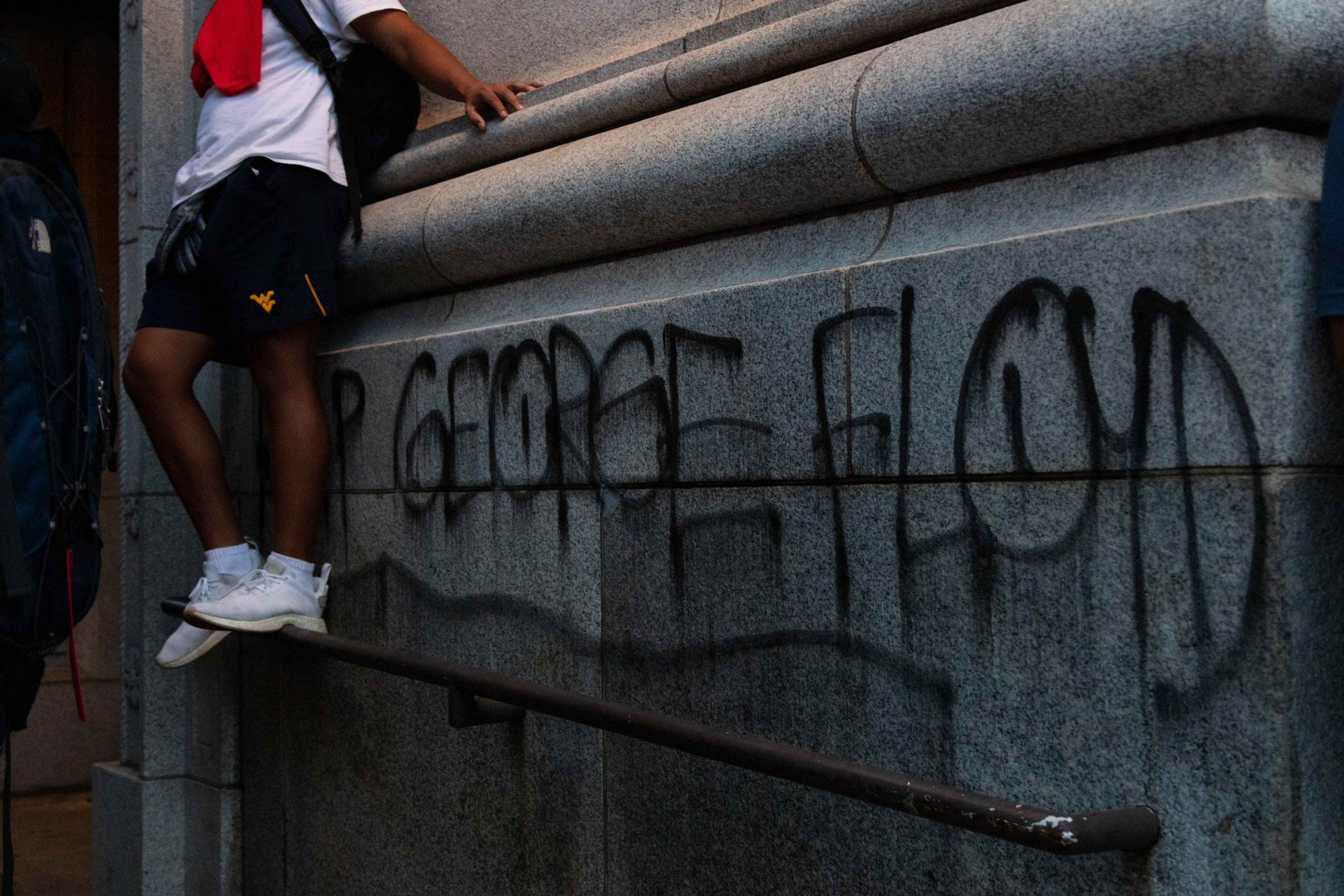A protester leans against a building where demonstrators spray painted the name of George Floyd.