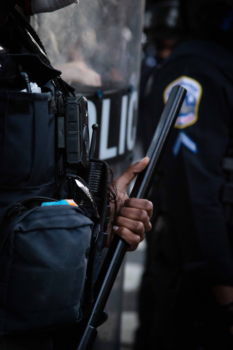 A police officer clutches her baton as she and her fellow officers create a wall to block protesters from nearing the White House.