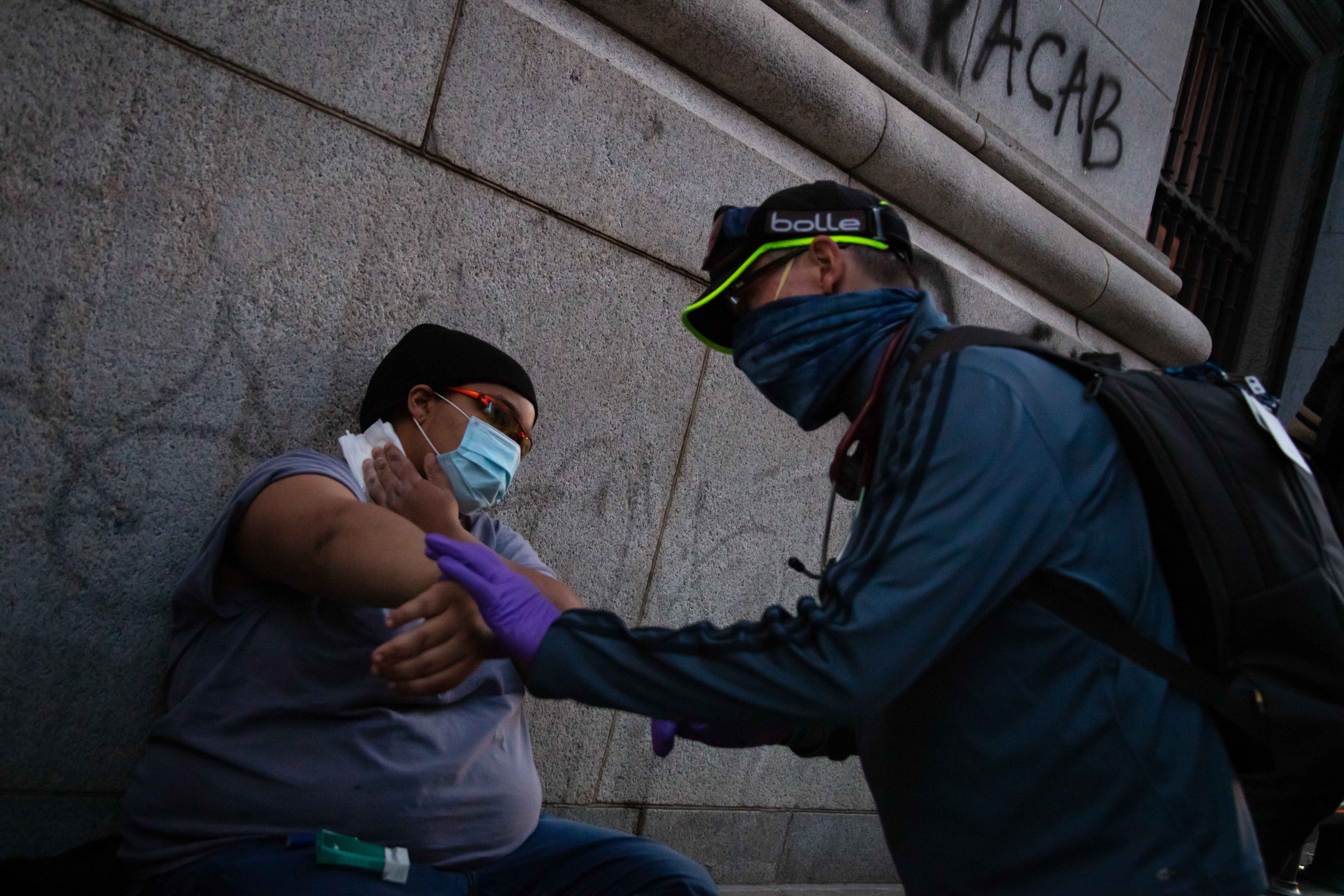John Lucas, a volunteer medic, treats a protester who was burned by a flash grenade.