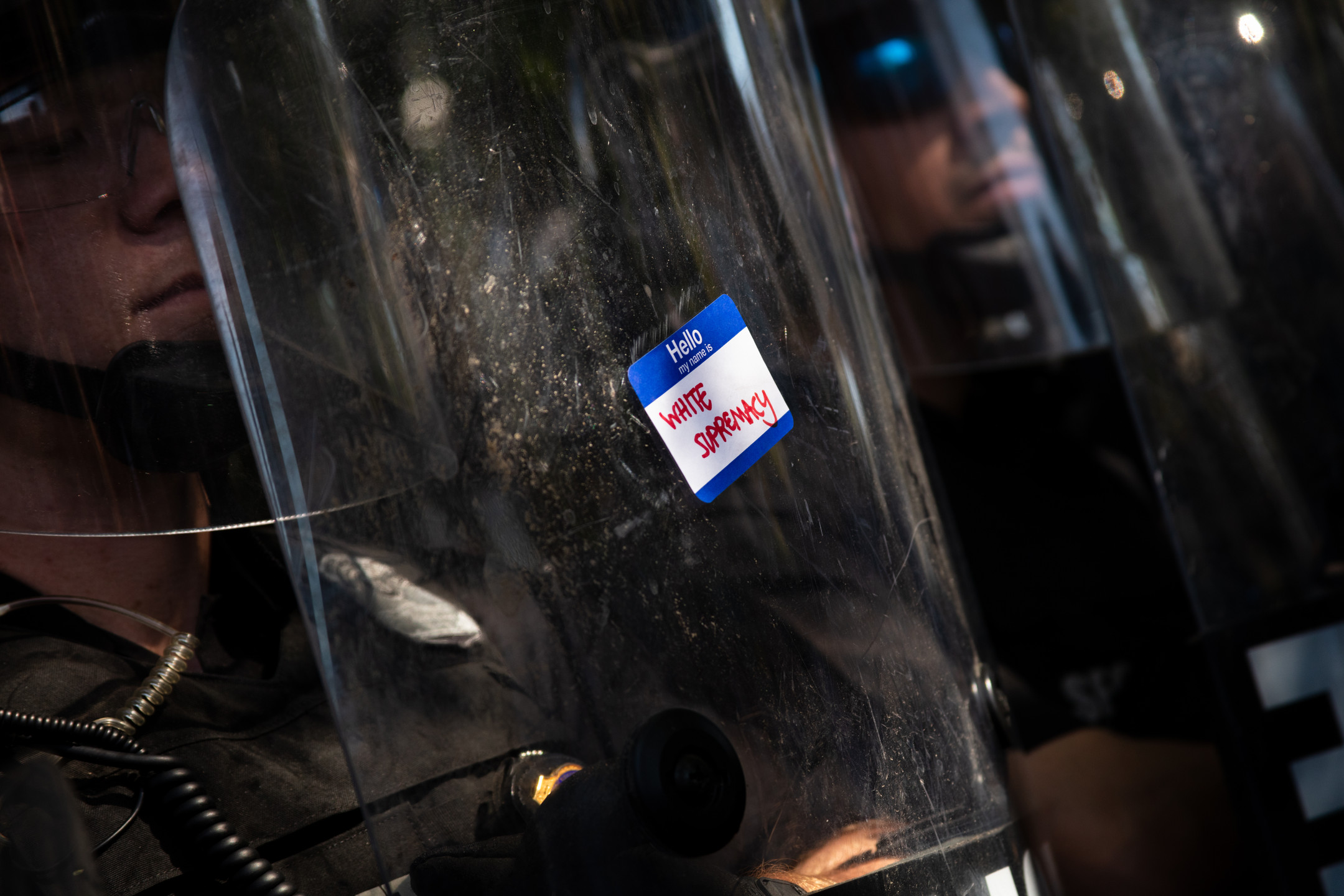 "A sticker reading ""Hello, my name is: White Supremacy"" that was placed on the shields of police officers as they faced off against protesters outside of the White House in Washington, D.C., May 30, 2020."