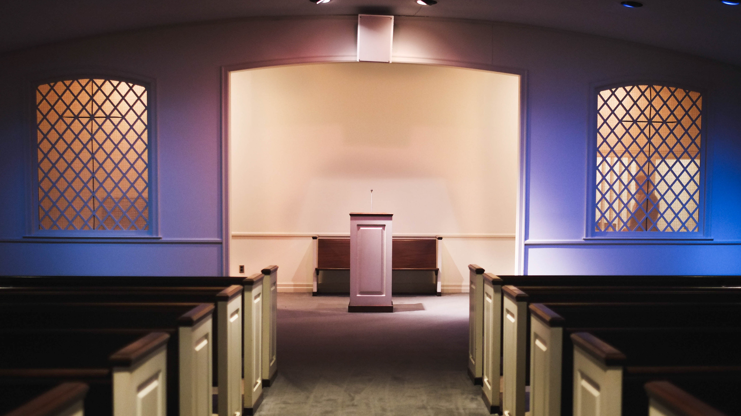 The chapel at Jordan Funeral Home is bathed in pink and blue lights. These colors are used to give the decedents a more lifelike appearance during open-casket funeral services.