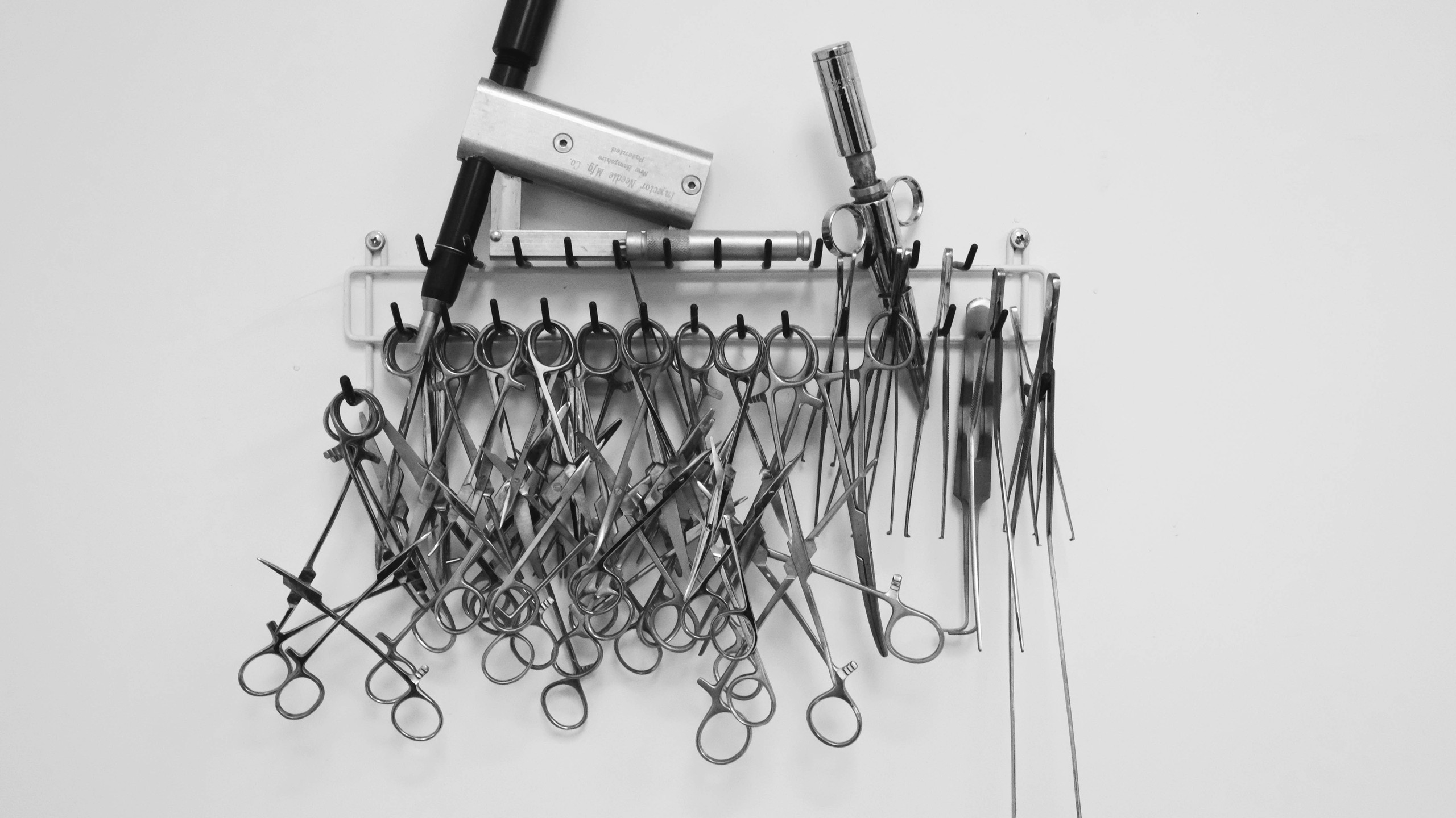 An array of medical scissors and instruments hang on the wall in the embalming room.