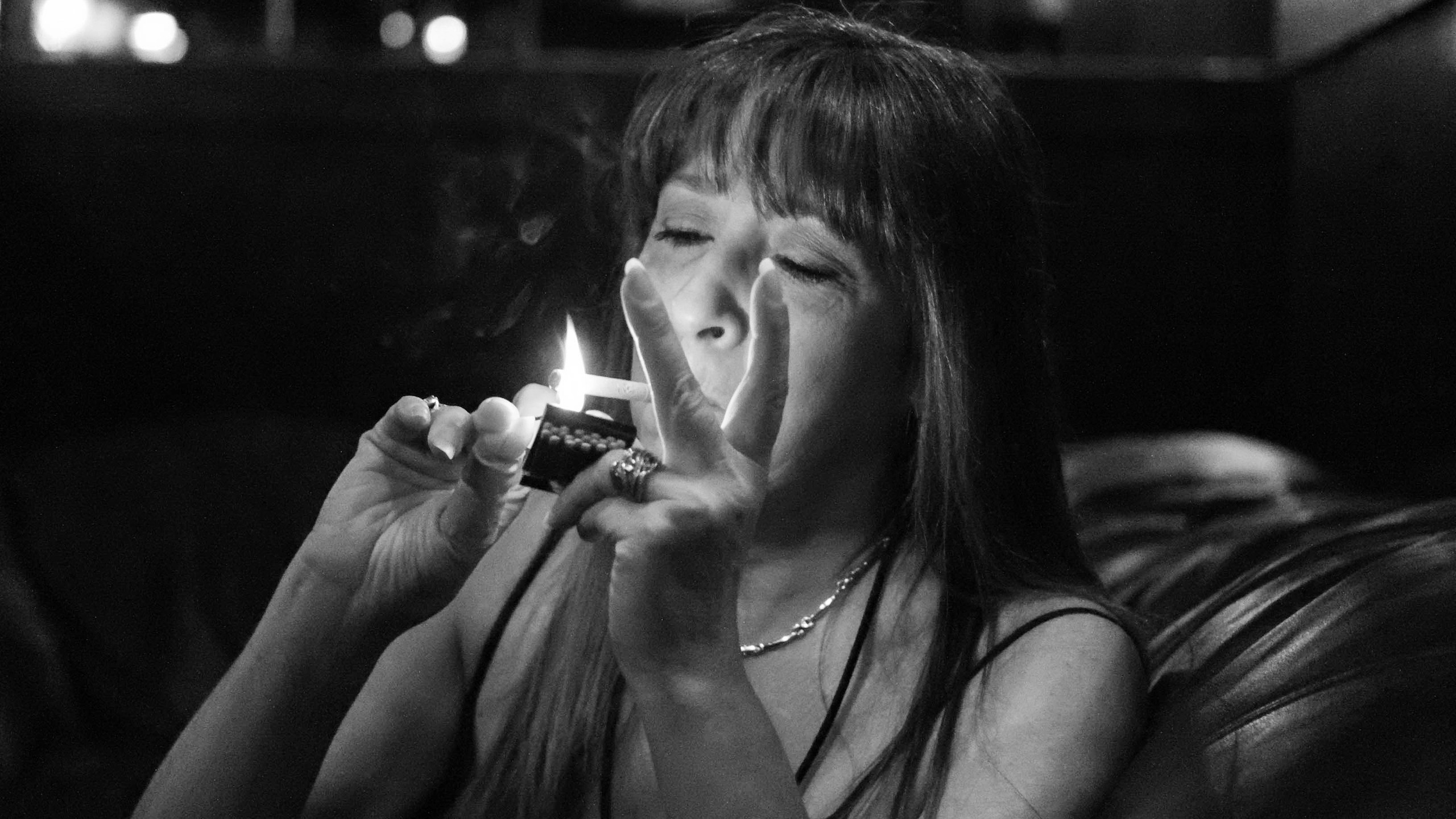 Charleen uses a Tattletale Lounge matchbook to light her cigarette while I interview her in one of the club's private VIP rooms.