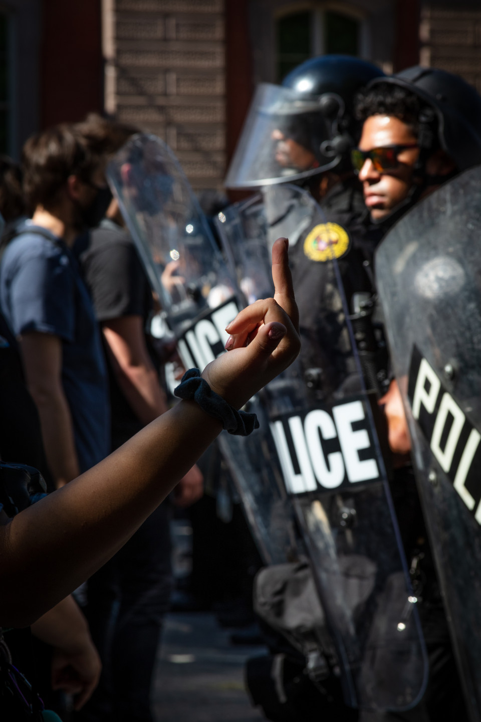 A protester gives the middle finger to a row of police officers in front of the White House in Washington, D.C., May 30, 2020.