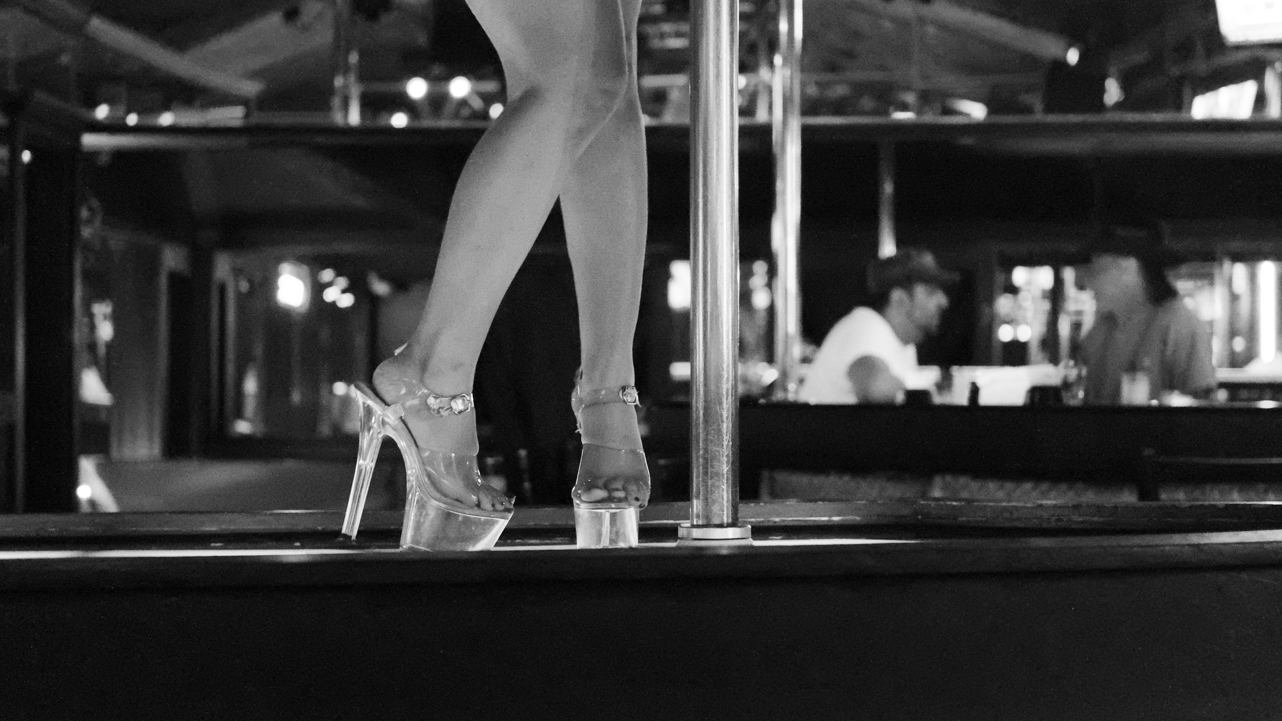 Sometimes strip clubs are just a place for guys to hang out with each other. In this image, while the dancer is (quite literally) the main focus, in the background you can see two customers at the bar talking to each other, completely oblivious to her naked body.