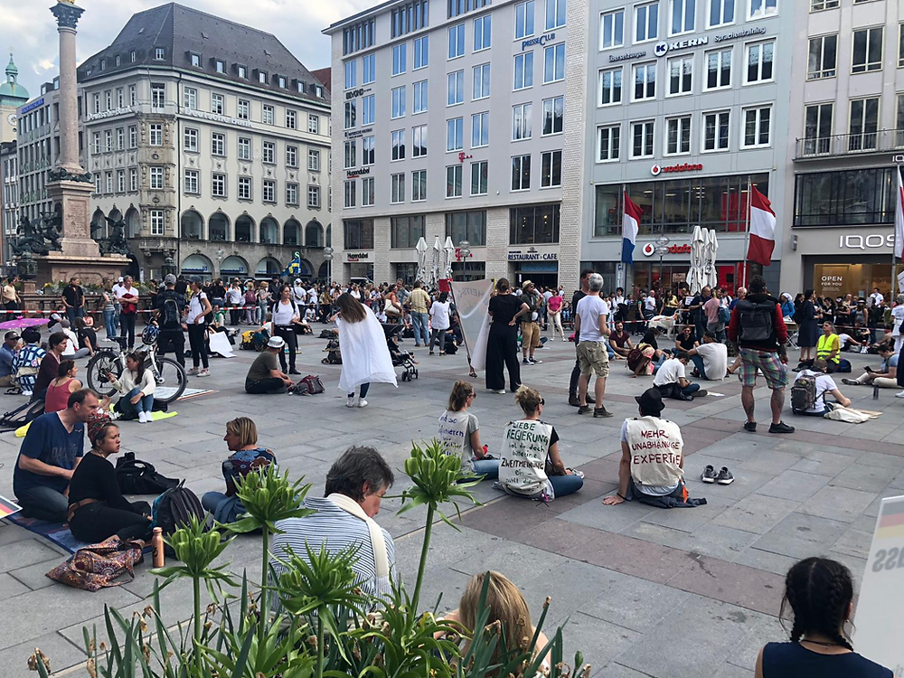Protesters seen staging a sit-down protest in Munich's Marienplatz.