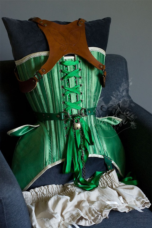 Steampunk Tinkerbell costume. Overbust corset with swing hooks, locking leather belt, hip petals, lace trim, and flossing. Green leather steampunk goggles, hip pouch, garter and jewelry.
