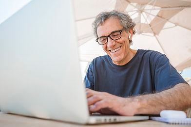 happy-senior-man-wearing-eyeglasses-usin