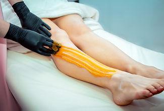 A woma waxing a leg
