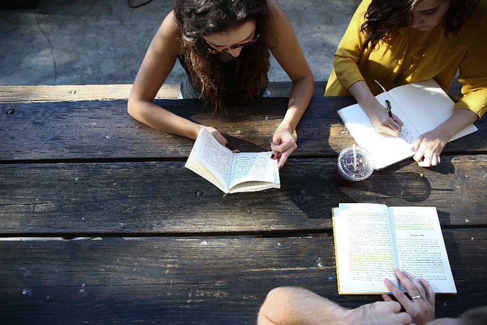 Three students study around a wooden picnic table.
